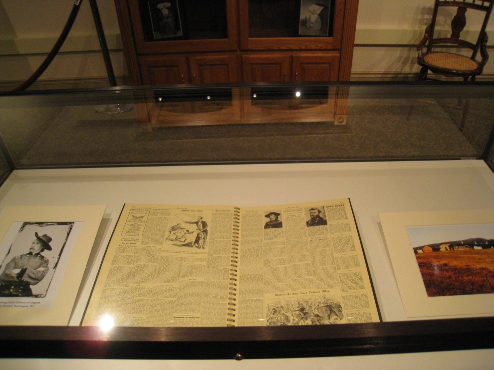 Center: reproduction newspaper with stories about the war. Left: Photo of George Armstrong Custer
