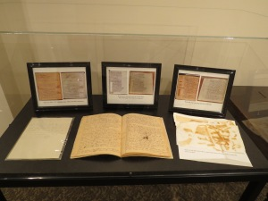 The newly-restored 1812 American Rule (front, center), now on display in the Provincial Archives. In the background are images of three of the restored pages