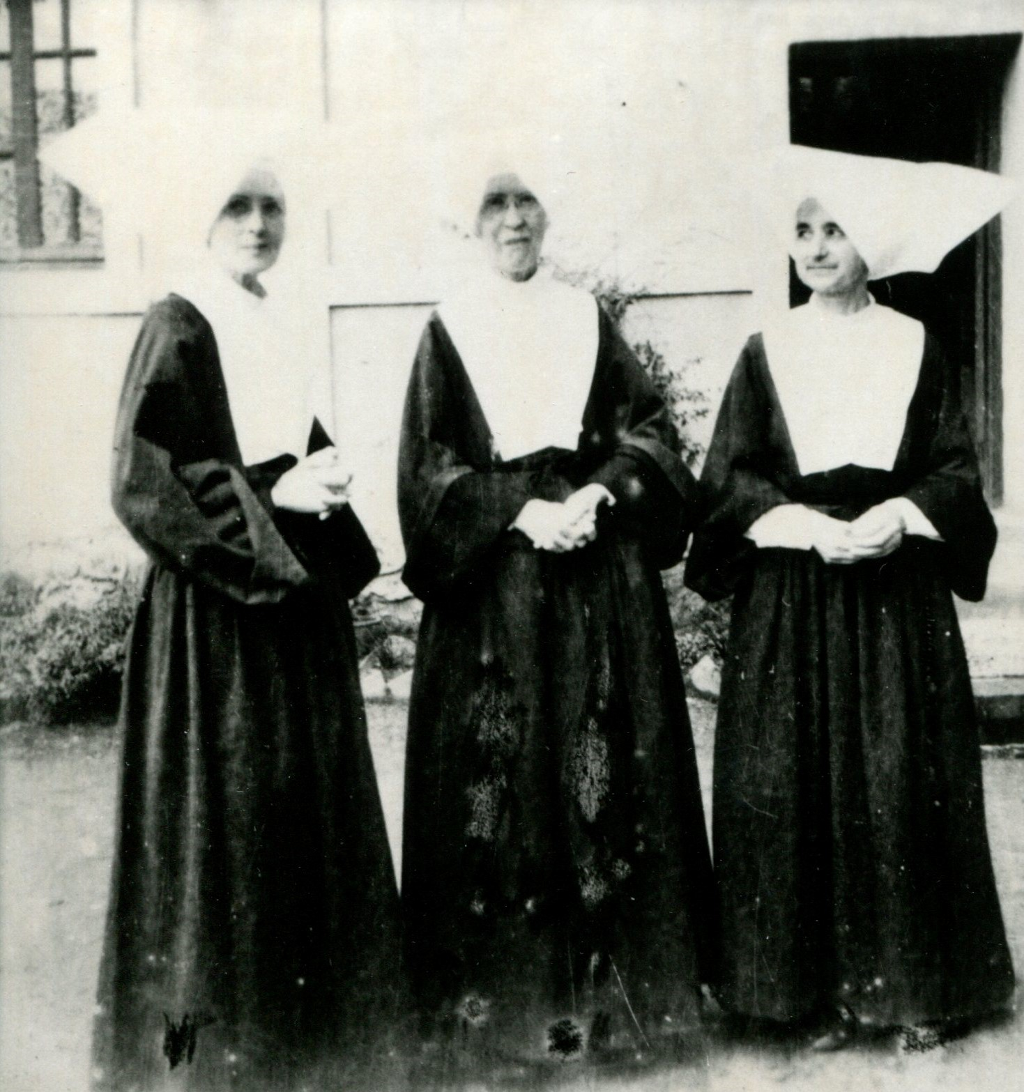 Sisters Clara Groell, Eugenia Biggs, and Catherine O'Neill outside barracks, Aug. 1945. These three sisters were missioned in China and ended up serving as U.S. Army nurses in the Pacific theater of World War II.
